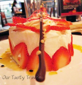 Another view of the pavlova decorated with whipped cream, strawberries, and drizzled passionfruit syrup